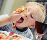 Child eats pizza in cafeю Royalty Free Stock Images