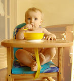 The child eats porridge. The child sits at a table and eats porridge royalty free stock photo