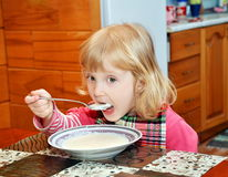 Child eats porridge for breakfast Royalty Free Stock Image