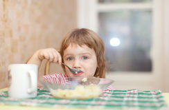 Child eats potato with spoon Royalty Free Stock Image