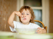 Child eats with spoon Royalty Free Stock Photo