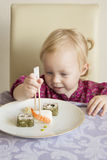 Child eats sushi, rolls,. Little girl eats her own sushi Royalty Free Stock Photo