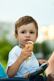 Child eats tasty ice-cream. Beautiful child eats tasty ice-cream stock photos