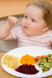 The child eats a vegetable salad Royalty Free Stock Images