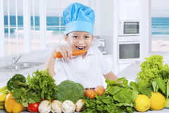 Child eats vegetables in the kitchen royalty free stock image