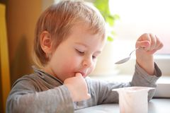 Child eats yogurt with a spoon sitting at the table. The child eats yogurt with a spoon sitting at the table Royalty Free Stock Image
