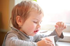 Child eats yogurt with a spoon sitting at the table Royalty Free Stock Photo