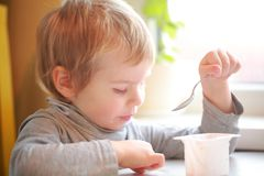 Child eats yogurt with a spoon sitting at the table Royalty Free Stock Photos