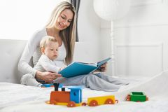 Child education. Happy mother with her toddler sitting on the bed and reading a book royalty free stock photos