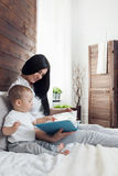 Child education. Happy mother with her toddler sitting on the bed and reading a book Stock Photos