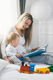 Child education. Happy mother with her toddler sitting on the bed and reading a book Royalty Free Stock Photo