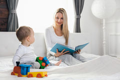 Child education. Happy mother with her toddler sitting on the bed and reading a book Royalty Free Stock Photography