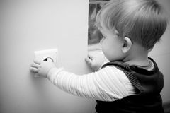 Child at electric socket. Dangerous situation - little child touching an electric socket in the wall Royalty Free Stock Photo