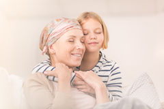 Child embracing ill mother Stock Photography