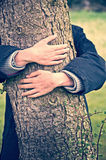 Child embracing a tree trunk Royalty Free Stock Image