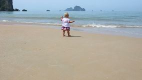 Girl in Ukrainian Costume Embroidery on Beach. Child in embroidery runs along the sandy beach to the sea on the background of the islands stock footage