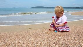Girl in Ukrainian Costume Embroidery on Beach. Child in embroidery sits on the shell beaches and played with stones on a background of the islands and the sea stock video footage