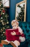 Child emotion gift box christmas tree untie ribbons. Child emotion with gift box near christmas tree untie ribbons royalty free stock images