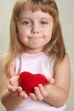Child emotions. Red heart in hands and slightly blurred child face ir background Stock Photography