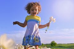 A child with emotions. Nature in summer. A child in a clearing with flowers. Little girl with flowers royalty free stock photo