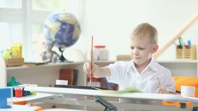 The child is engaged in creativity. Boy painting with watercolors stock footage
