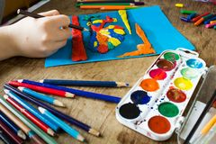 Child is engaged in creativity. The child is engaged in creativity. Sculpts from clay draws pencils and paints Royalty Free Stock Image