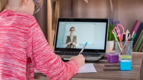 The child is engaged at home, in front of her laptop with an online lesson