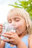 Child enjoy drinking water outdoors Royalty Free Stock Images