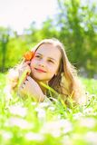 Child enjoy spring sunny day while lying at meadow.Seasonal allergy concept. Girl on dreamy face holds red tulip flower stock photos