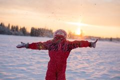 Child enjoying the falling snow. In the sun Stock Photos