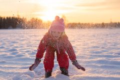 Child enjoying the falling snow. In the sun Stock Photography