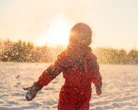 Child enjoying the falling snow. In the sun Stock Image