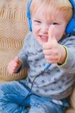 Child wearing headphones to listen to music stock image