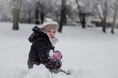 Child enjoying a winter atmosphere. Happy child ennjoying winter atmosphere in park covered by snow Stock Image