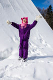 Child enjoying winter time. Happy smiling little child in purple overall and snow Royalty Free Stock Photo
