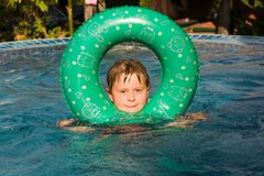 Child enjoys swimming with rubber ring Stock Photography