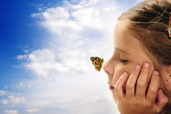 Child and environment. Butterfly resting on the nose of a small girl with closed eyes, concept for dreams, positive future, environment, imagination and