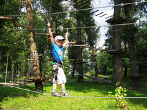 Child equipped climbing in rope park Royalty Free Stock Photos