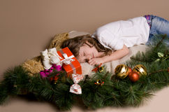 Child  on eve of Christmas. Child is lying and dreaming near tree decorations on eve of Christmas Royalty Free Stock Images