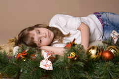 Child  on eve of Christmas. Child is lying and dreaming near tree decorations on eve of Christmas Stock Image