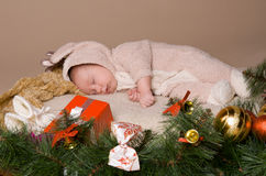 Child  on eve of Christmas. Child is lying and dreaming near tree decorations on eve of Christmas Stock Photo