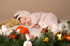 Child  on eve of Christmas. Child is lying and dreaming near tree decorations on eve of Christmas Royalty Free Stock Photo