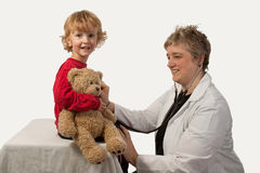 Child examination. Young caucasian boy holding brown teddy bear getting a medical examination from a short hair woman in doctor uniform holding a stethoscope royalty free stock images