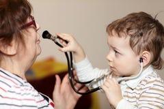 Child examines grandmother using stethoscope Stock Photos