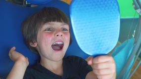 Child looks at his teeth through the mirror. Child examines his teeth in the mirror, sits in a dental chair stock footage