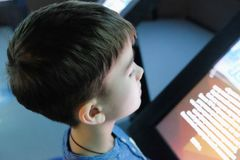 Child examines the touchscreen. In the interactive Museum Stock Photos
