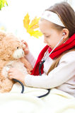 Child is examining her teddy bear Stock Photography