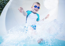 Child excited and having fun going down a waterslide Stock Image