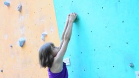 Child exercising at bouldering gym stock video footage