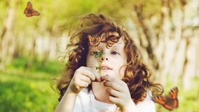 The child explores the nature. Curly girl looking at a butterfly on wild flower. The child explores the nature Royalty Free Stock Photo